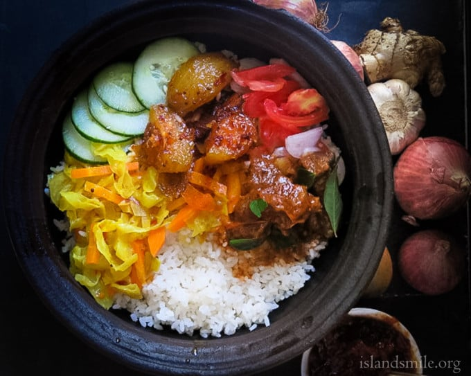 rice with cabbagge and carrots cooked in coconut milk,ambarella curry , spicy beef with a onion and tomato salad